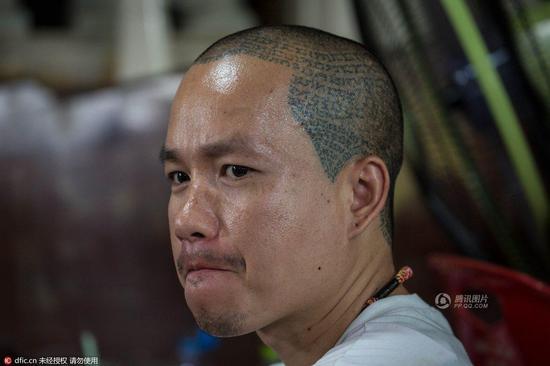 一名男子头部沿着发际线纹着经文图案