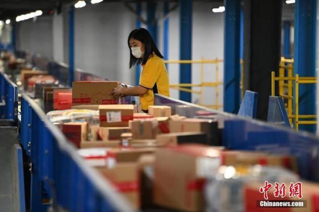 物流工人对网上下单的商品进行分拣、装车。 中新社记者 崔楠 摄